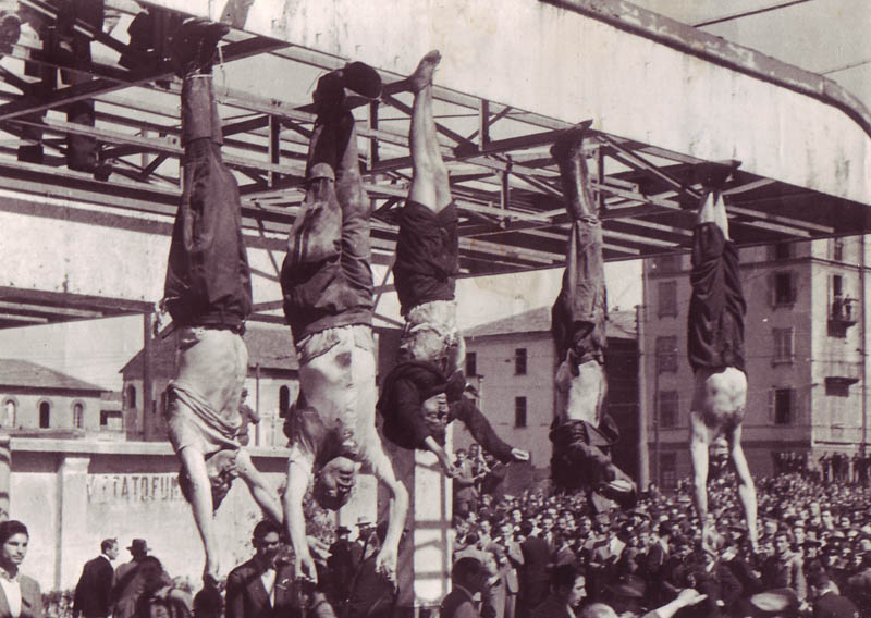 BENITO MUSSOLINI HANGING BY HIS HEALS NEXT TO HIS MISTRESS